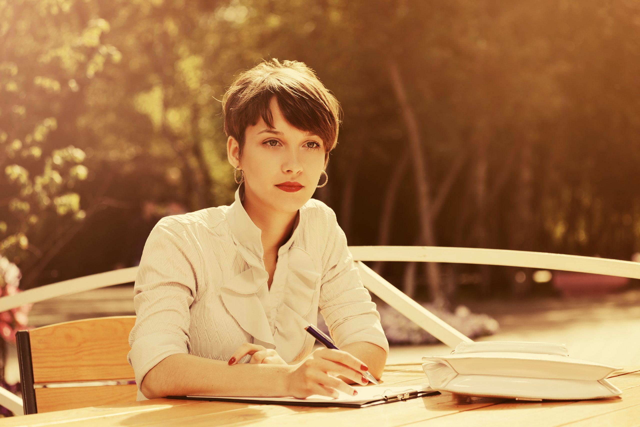 Vrouw buiten aan een tafel aan het schrijven